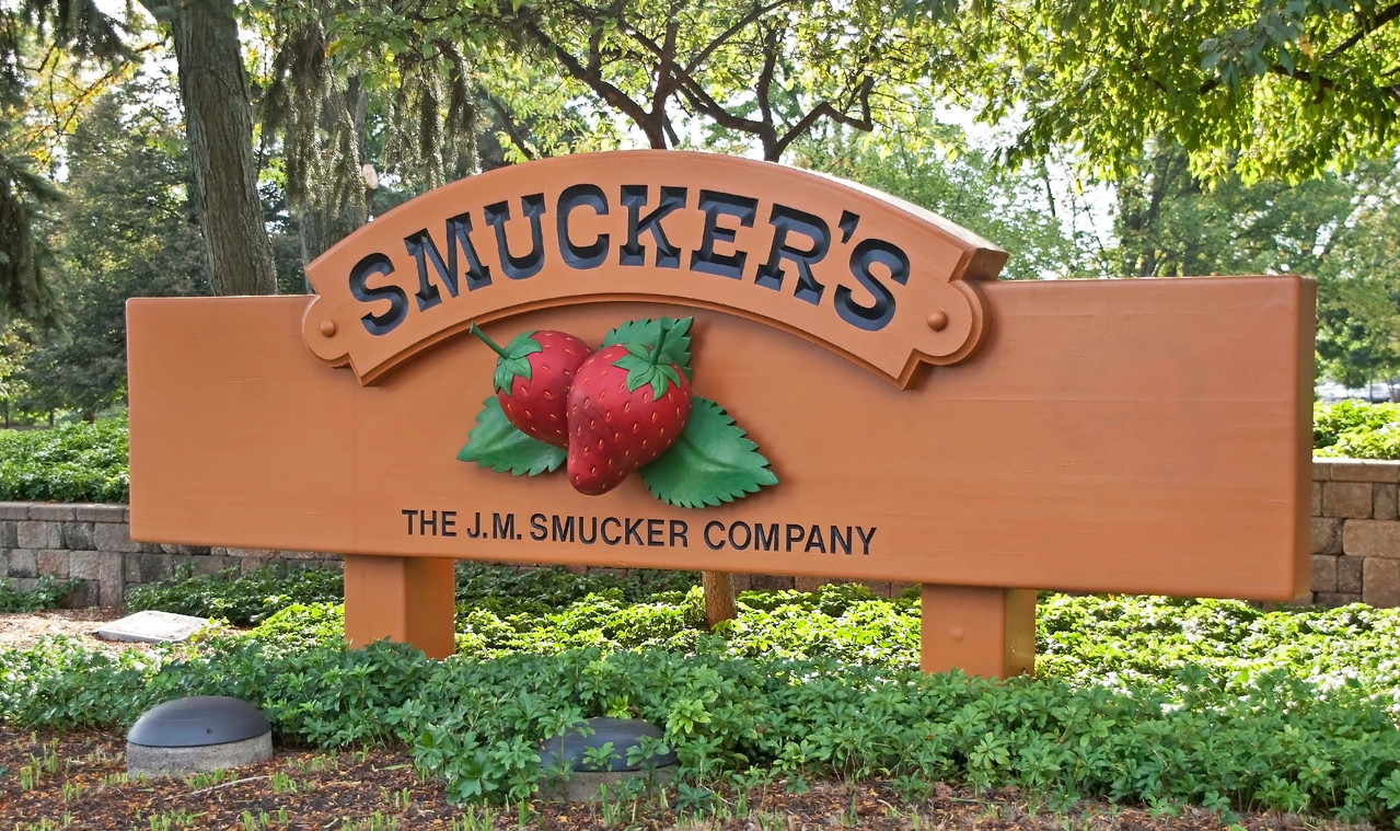 Photo: J. M. Smucker Company corporate headquarters sign at the entrance of the company's complex in Orrville, Ohio.  General Description: The J. M. Smucker Company (www.smuckers.com) was founded in 1897 when the Company's namesake and founder sold his first product -- apple butter -- from the back of a horse-drawn wagon. Today, over a century later, The J. M. Smucker Company is the leading marketer and manufacturer of fruit spreads, peanut butter, shortening and oils, ice cream toppings, sweetened condensed milk and health and natural foods beverages in North America.  Roles in Wayne County's Ag-Bio Cluster: Leading food products producer, major corporate headquarters, product development and innovation, leading brand generator for Wayne County's ag-bio and food products cluster.   Website: http://www.smuckers.com/