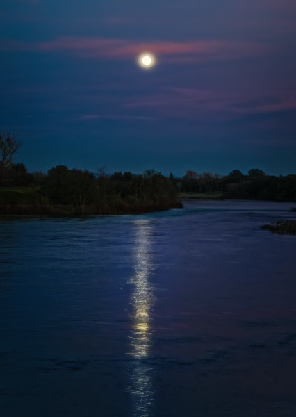 The moon rising over the American River