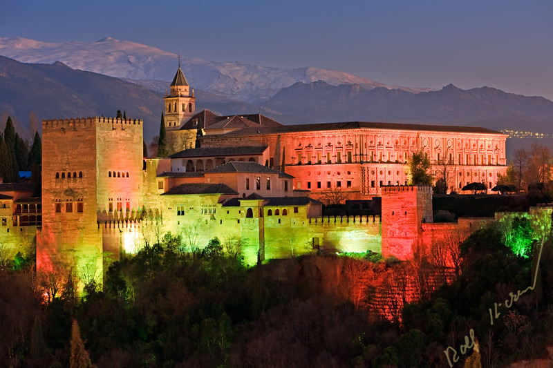 The Alhambra (La Alhambra) a moorish citadel and palace designated a UNESCO World Heritage Site in 1984, backdropped by the snowcapped Sierra Nevada mountain range seen from Mirador de San Nicolas in the Albayzin district at dusk, City of Granada, Province of Granada, Andalusia (Andalucia), Spain, Europe.