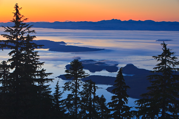 View from Vancouver Island North over Hanson Island, Stubbs Island, Malcolm Island, Donegal Head over Queen Charlotte Strait towards the British Columbia Coastal Mountains at twilight, dusk with fog banks creeping over the islands, British Columbia, Canada.