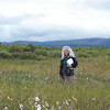 """Randy Meyers with her """"vasculum,"""" or herbarium specimen container, under her arm. She is standing in a wet meadow of tall cottongrass - Eriophorum angustifolium (ERAN6), tussock cottongrass - Eriophorum vaginatum (ERVA4) and wideleaf polargrass - Arctagrostis latifolia (ARLA2). Photo by BLM AK."""