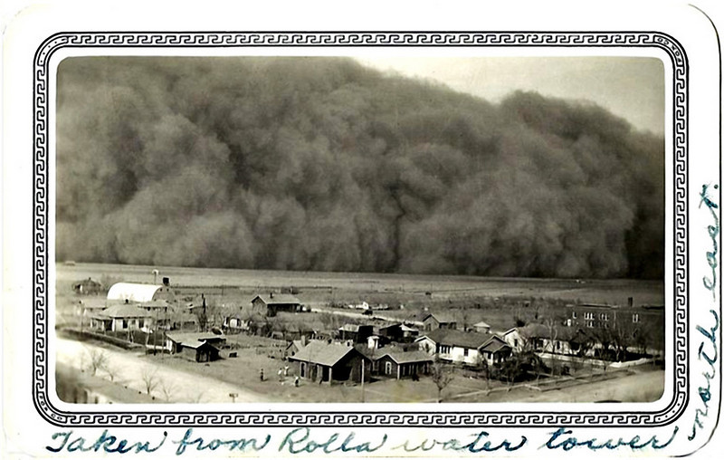 "Dust Storm, Rolla, Kansas, April 14, 1935. Gelatin Silver Print Snapshot. From the verso: ""Dear friends: - This is one of the ""cow chokers"" we had April 14 - 35. and was it bad?"" A copy of this print was sent to President Roosevelt with a note that read, ""Dear Mr. Roosevelt, Darkness came when it hit us. Picture taken from water tower one hundred feet high. Yours Truly, Chas. P. Williams."""