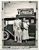 "Family at Gas Station, Corona, NM 1938. Gelatin Silver Print Snapshot. Handwritten in lower margin: ""Will & Hannah Greenwood & Bonnie & Aufrey Edwards, Feb 1938."" On verso in a juvenile hand: ""Lina's picture, don't give away. dady and me and Bonie Mae Edwards & Aufrey Martin Edwards. Made in Febuary 1938. Bonie Mae is 3 months old now and weighs 13 lbs."""