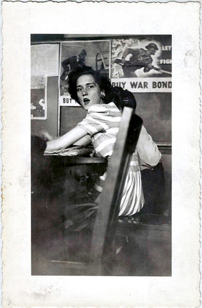 Young Woman Surprised at Table with War Bonds Posters on the Wall, c. 1944. Gelatin Silver Print Snapshot