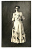 Woman with Pictures Attached to her Dress, c. 1910. Real Photo Post Card
