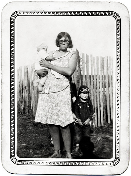 Young Mother with Infant and Small Boy Wearing Aviator Helmet and Goggles, c. 1940s. Gelatin Silver Print Snapshot