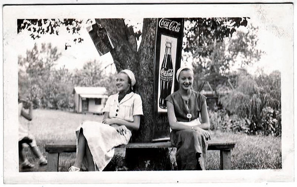 Identical Twin Sisters and Coca Cola Sign, c. 1920s. Gelatin Silver Print Snapshot
