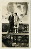Lionel Barrymore and his Wife Irene Fenwick in Front of a Louise Brooks Billboard, c. 1920s. Gelatin Silver Print Snapshot