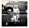 Baby in Stroller with Truck in the Background, c. 1940s. Gelatin Silver Print Snapshot