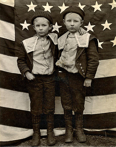 Identically Dressed Brothers in front of American Flag, c. 1900. Gelatin Silver Print