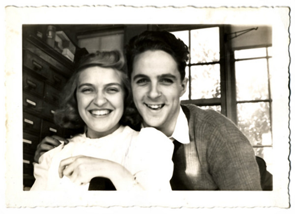 "Happy Couple, Morristown, NJ, 1941.  Gelatin Silver Print Snapshot. Handwritten on verso: ""Byron Nichols, Jr. and Ruth Wilkins around 1940. In sun porch office of Nichols Products Co, 19 Colonial Ave, Morristown, NJ"" Also on verso processor's stamp dated Nov 17, 1941."