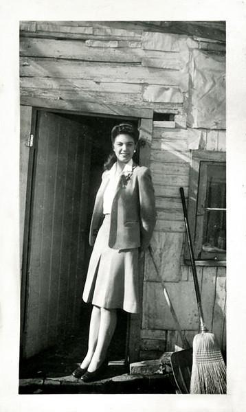 Classy Young Woman in Doorway of Primitive Cabin, c. 1950s. Gelatin Silver Print Snapshot