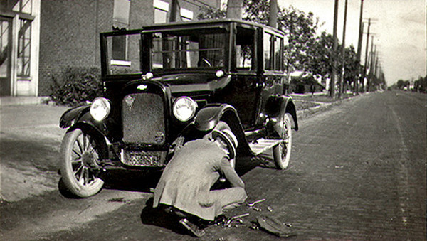 Changing a Flat Tire on 1924 Chevy, c. 1920s. Gelatin Silver Print Snapshot