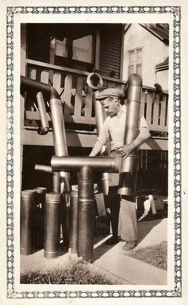 Pipe Fitter with Stove Pipes, c. 1930s. Gelatin Silver Print Snapshot