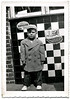 Boy Wearing Winter Coat and Cap in Front of a Diner, c. 1950s. Gelatin Silver Print Snapshot