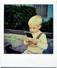 Young Boy Viewing a Polaroid SX70 Photograph, c. 1980s. Polaroid SX70 Print