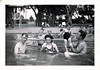 "A Day at the Lake, 1947. Gelatin Silver Print Snapshot. Written on verso: ""Aug 10, 1947 White Rock Lake (Curwin eating cookies)"" [with an arrow on the back indicating the little boy at the picnic table near the trees]."