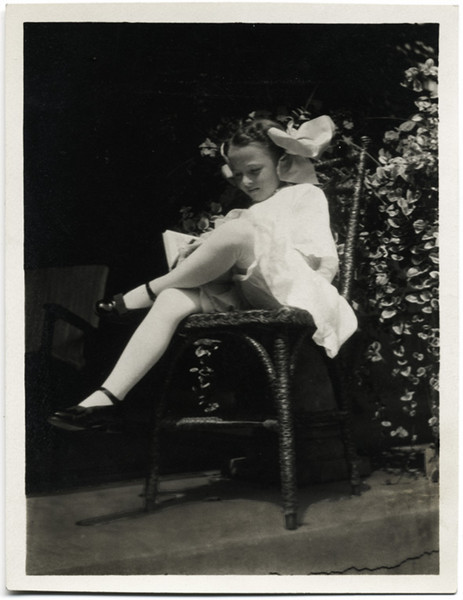 Elegant Young Girl Sitting on a Porch on a Straight Backed Chair Reading, c. 1910. Gelatin Silver Print Snapshot.