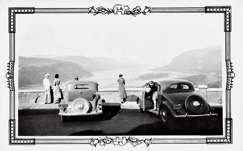 Tourists Viewing the Columbia Gorge from Vista House at Crown Point on the Columbia River Highway, Oregon, 1936. Gelatin Silver Print Snapshot. (Note that both of the cars sports a rumble seat.)