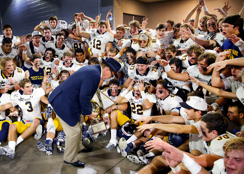 Highland Park football players are overwhelmed with excitement as head football coach Randy Allen places the winning trophy for a team photo after their Class 5A Division I Region II final win over Mansfield Legacy at AT&T Stadium in Arlington, Texas, Friday, December 2, 2016. Highland Park went on to win the State title.