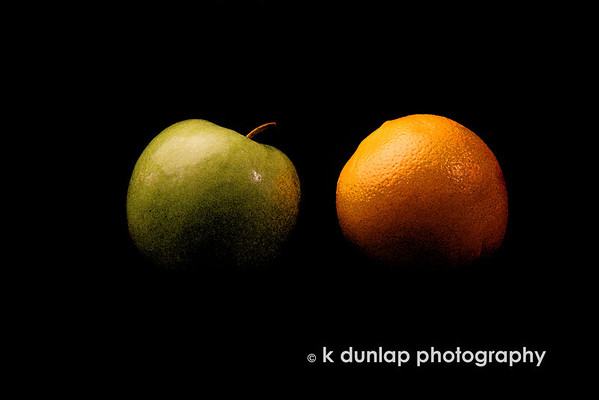 "01.07.09 = Apples and Oranges<br /> After shooting and processing these two, I have a whole new appreciation for the saying ""Comparing Apples to Oranges.  The orange kept rolling around, until I used a little stick um' under it. The apple has a funny little tilt to the side, but it you photographed the backside, it had a large dent in it.  While processing this image the tone and color was all out of whack. The smooth skin of the apple vs. the texture of the orange also gave me some fits.  Again, I have a new appreciation for that saying.  <br /> <br /> Thanks again to all my fellow Smuggers.  I really am having a lot of fun with this series and so glad you are enjoying it.  A fellow Smugger asked to see my set-up and I am always happy to share what I do. I will get some more shots of my set up and create a new gallery.  I'll let you know when I get it up.  (Probably not until the weekend.)<br /> <br /> A hit for tomorrow's post:  Fuzz."