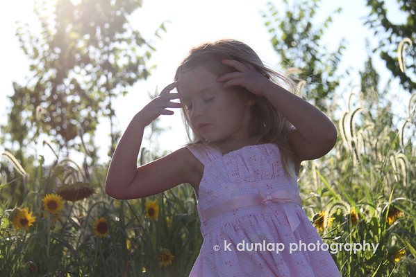 "07.30.10 = Summer<br /> <br /> This photo is the daughter of a friend of mine, that I photographed on Monday.  It was a wonderful shoot and there are so many great photo's to choose from.  This is one of my favorites because, well, it just says Summer to me.  Little girls in sundresses playing in a field of flowers; timeless.  The quote captures the whole feeling.  Have a great weekend!<br /> <br /> ""Then followed that beautiful season…Summer…Filled was the air with a dreamy and magical light; and the landscape lay as if new created in all the freshness of childhood.""  Henry Wadsworth Longfellow"