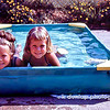 "07.06.12 = Flashback Friday – Little Mermaids - 1965'ish<br /> <br /> I love this photo of my two older sisters in our little kiddy pool on the driveway.  We had that little pool for many years until we graduated to the sprinkler and then on to the neighborhood pool.  I can't begin to guess just how many hours I spent in a pool as a kid.  With pool's and sprinklers came bathing suites,  beach towels, toys and that old familiar smell of Coppertone.  On Saturdays we would go as a family to the neighborhood pool.  We loaded up the Ford Country Squire with all the blow-up floaties, the big cooler, the family beach bag and plenty of beach towels.  We would all walk in carrying something and then the hunt began for a good spot and few lounge chairs to claim it with.  Who remembers adult swim and Marco Polo?  Laughter, the life guard's whistle, the sound of a big splash, the hot pool deck on the bottom of your feet, the feeling of water dripping off you as you stand there asking your Dad for .10 cents for a snow cone…Ahh, the sounds and the feeling of summer. <br /> <br /> ""Live in the sunshine, swim the sea, drink the wild air.""  Ralph Waldo Emerson"