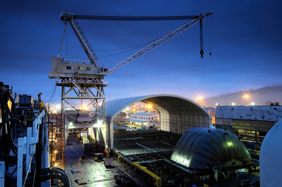 Crane illuminated with Christmas lights, barge under construction.