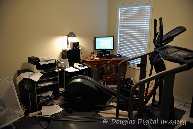 """January 17th - January 23rd<br /> <br /> So I was working from home on Thursday the 14th and I decided to take a picture of our home office/workout gym.  As you can see we have a treadmill, an elliptical, a desk with a 22"""" LCD on it.  The LCD, keyboard, and mouse are hooked up to a DVI KVM switch that allows me to switch between my Desktop computer (that the lamp is sitting on) and my work laptop.  <br /> <br /> To the left is our HP Printer/Scanner/Fax machine that gets a lot of use.  The room is a bit cramped, but it gets the job done.<br /> <br /> D700; 28-70 f/2.8 AF-S"""