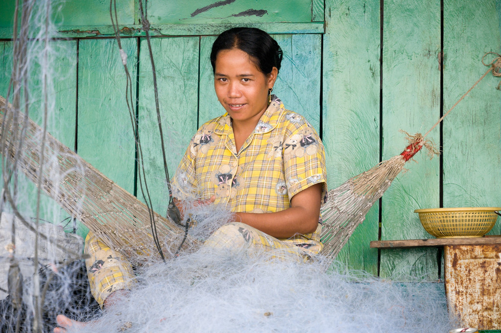 A Koh Roung village woman restrings Sihanoukville fishermen's nets on her front porch. The village was initially established in 1992 for crabbing, but the supply dried up and villagers had to look elsewhere for money. This is one of only a few job opportunities left in the village.