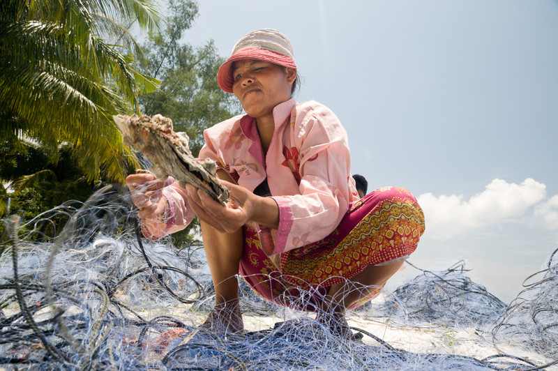 A Koh Roung village woman cleans the detritus out of Sihanoukville fishermen's nets on the beach. The dead animals, mostly crabs and starfish, are thrown into a nearby stream that, by the time it reaches the ocean, is dark with human and animal waste.