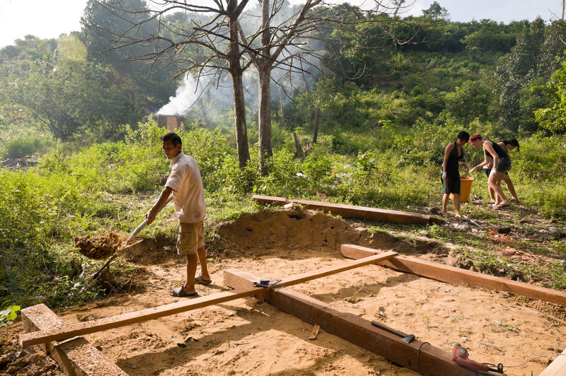 Mr. Sroy, the man hired to help build two toilets for the village, clears brush away from the build site. Members of Operation Groundswell, a Canadian volunteer organization, work at right to pick up and incinerate the village's trash.