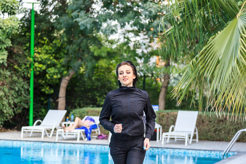 Panning shot of a beautiful woman running next to a swimming pool coming towards camera in Dubai, UAE.