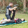A young and healthy personal trainer is working with his client outdoor on the grass in Dubai, UAE.