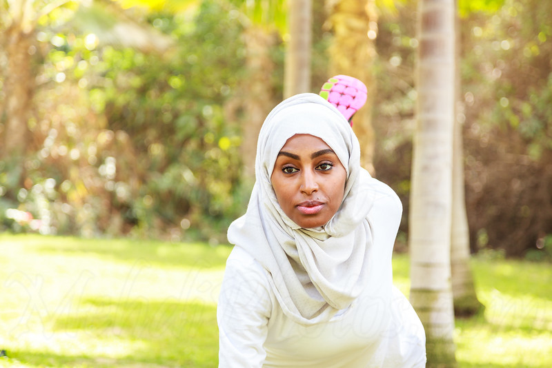 A healthy and happy African Muslim woman in hijab is doing a workout outdoor in a white shirt in Dubai, UAE.