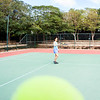 Woman tennis player practice in tennis court in Dubai with a tennis ball in the foreground.
