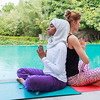 Two women one in hijab are practicing yoga back to back outdoor in pair in Dubai, UAE.