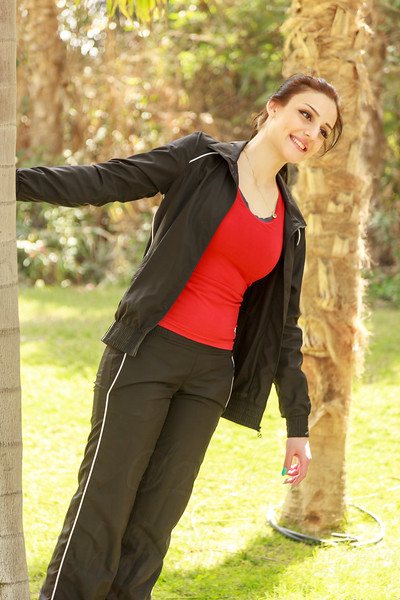 A beautiful and healthy woman is standing next to a tree in a park after a fitness workout in Dubai.