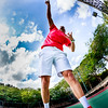 A tennis coach is practicing an smash next to the net while jumping. Enhanced version taken with fisheye.