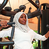 A healthy and happy African Muslim woman in hijab is practicing a workout in a gym.