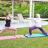 Two women practicing yoga outdoor in pair in a green area