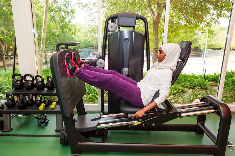 Beautiful Muslim Woman Using a Gym Machine.