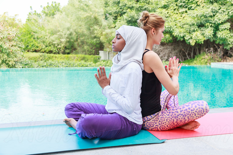 Two women practicing yoga outdoor in pair next to a swimming pool, back to back