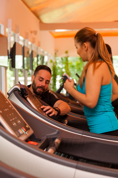 A young and healthy personal trainer is working with his client indoor on treadmill in Dubai, UAE.