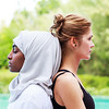 Two women one in hijab are practicing yoga back to back outdoor in pair close up