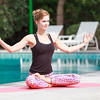 Beautiful Mid Adult Yoga Instructor is Practicing Yoga Outdoor next to swimming pool