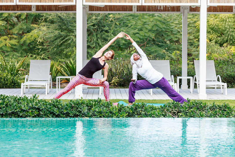 Two women practicing yoga outdoor in pair in a green area next to swimming pool