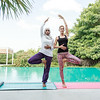 Two women practicing yoga outdoor in pair, next to each other with the tree pose