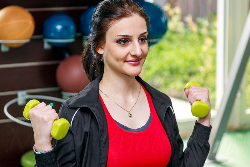 An beautiful and healthy woman is posing with a weight in hand in a gym after a workout in Dubai, UAE.