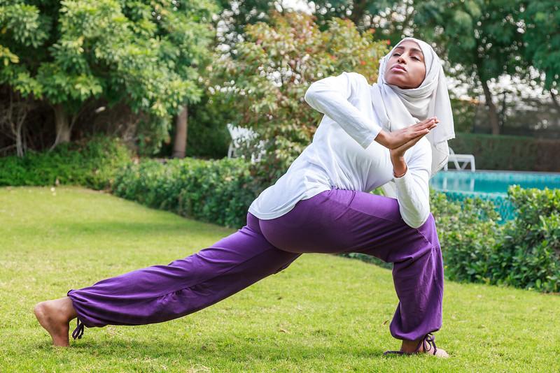 Beautiful Muslim Lady in hijab is Practicing Yoga Outdoor in Dubai, UAE.